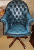 A buttoned blue leather upholstered swivel desk chair