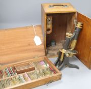 A Negretti and Zambra cased brass microscope and various specimen slides