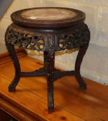 A 19th century Chinese carved hardwood marble top jardiniere stand, 48cm diameter, H.48cm