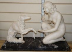 An Art Deco white marble model of a nude with a dog, after Chiparus, width 62cm height 42cm (a.f.)
