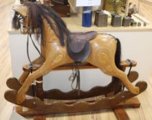 An Ian Armstrong carved rocking horse with brown leather tack
