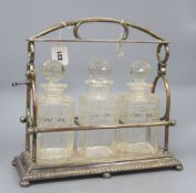 A late Victorian silver plated three decanter tantalus