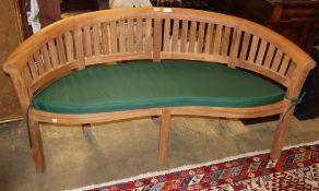 A teak garden banana bench with green cushion seat, W.160cm, D.56cm, H.83cm