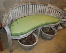 A weathered teak garden banana bench with cushion, W.160cm, D.60cm, H.85cm