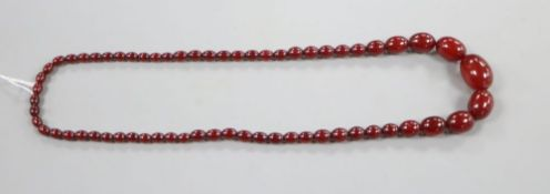A single strand graduated simulated cherry amber oval bead necklace, 69cm, gross 54 grams.