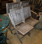 A set of six weathered teak folding garden chairs