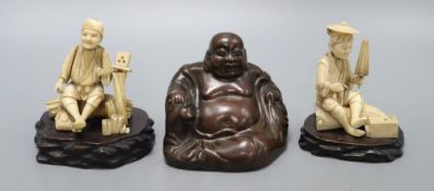 A Chinese bronze figure of a Budai and two Japanese carved ivory figures on stand