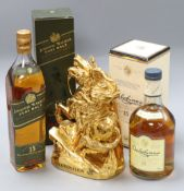 An ornate bottle of Coronation XO cognac and two bottles of whisky