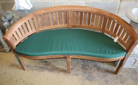 A teak garden banana bench with cushion seat, W.160cm, D.54cm, H.85cm