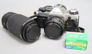 A cased Canon AE-1 programme camera with a 50mm lens, together with a 75-200mm zoom lens, also Canon