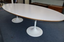 Martino Gamper. An oval white laminate and ply table on two aluminium circular bases, W.250cm, D.