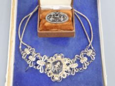 A Siamese filigree white metal and niello necklace and a marcasite brooch.