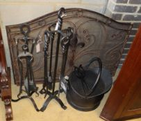 A wrought iron companion set, a coal helmet and a pair of wrought iron and mesh fire guards,
