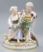 A Meissen figure group of a boy and girl with cage and garland, underglaze blue crossed sword marks,