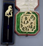 A carved ivory 'rearing horse' stick pin and a carved ivory panel pendant? 55mm.