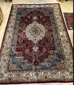 A Persian style burgundy ground small carpet 281 x 183cm