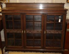 A 1920's carved oak three door bookcase, W.152cm, D.36cm, H.120cm