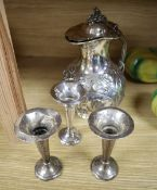 Three George V silver spill vases, height 11cm and a Victorian silver plated water jug