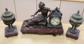 An early 20th century spelter clock garniture, on rouge marble plinths, clock width 44cm