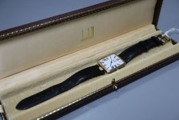 A gentleman's stylish silver gilt Dunhill quartz wrist watch, with Roman dial, on leather strap with