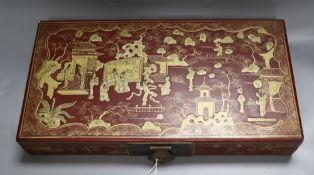 A Chinese red lacquer box, gilded with figures and landscape, width 38cm