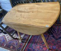 An Ercol light elm and beech circular drop leaf dining table, width 110cm, depth 127cm extended