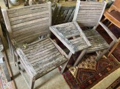 A weathered teak love seat,, width 148cm, in need of repair
