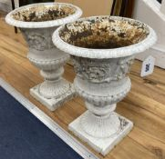 A pair of white painted cast iron campana-shaped urns, height 37cm