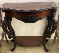A Victorian carved walnut serpentine front two tier console table with hinged top, width 98cm, depth