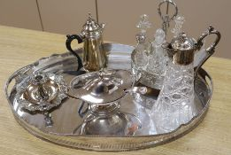 A quantity of plated wares including a seven bottle cruet, a claret jug and a large oval tray,