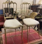 A pair of brass side chairs with padded seats