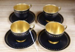 A set of four miniature Royal Worcester cups and saucers, in black and gilt design