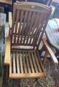 Six teak folding garden armchairs with cushions, an octagonal weathered teak folding garden table,
