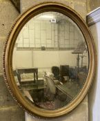 An early 20th century oval giltwood and gesso wall mirror, width 60cm height 70cm
