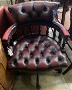 A reproduction tub shaped swivel desk chair upholstered in buttoned burgundy leather