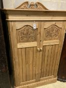 A Victorian style carved pine two door dwarf cabinet, width 98cm, depth 56cm, height 150cm