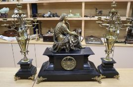 Moreau. A Victorian clock garniture, surmounted with a bronze figure, on black slate plinths,