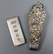 A silver money clip and a white metal chatelaine clip.