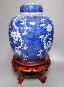 A pair of large Chinese blue and white 'prunus' jars and covers, early 20th century, wood stands,