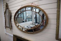 An Edwardian oval gilt marginal framed wall mirror, 111 x 74cm