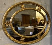 An oval gilt carved wood framed wall mirror with marginal plate, 92 x 71cm