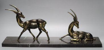 Two Art Deco cast gilt metal gazelles, on black veined marble plinth, 55cm