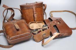 A pair of cased opera glasses, two pairs of cased binoculars and a Zeiss Ikon Nettar cased camera