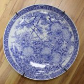 A large Chinese porcelain wall plate, painted with birds and flowering shrubs in underglaze blue