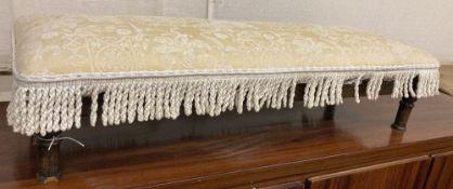 An oak framed fender stool, with cream brocade upholstery, width 110cm, depth 38cm, height 24cm