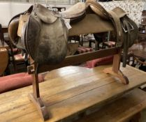 Two tan leather saddles on a pine saddle stand
