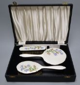 A three piece silver plated translucent enamelled dressing table set, cased