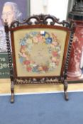 A Victorian rosewood firescreen with armorial tapestry banner, width 75cm, height 105cm