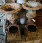 A pair of Victorian style cast iron campana garden urns on stands, height 49cm