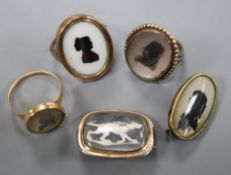 Three assorted Victorian yellow metal and glazed silhouette rings and two brooches, including